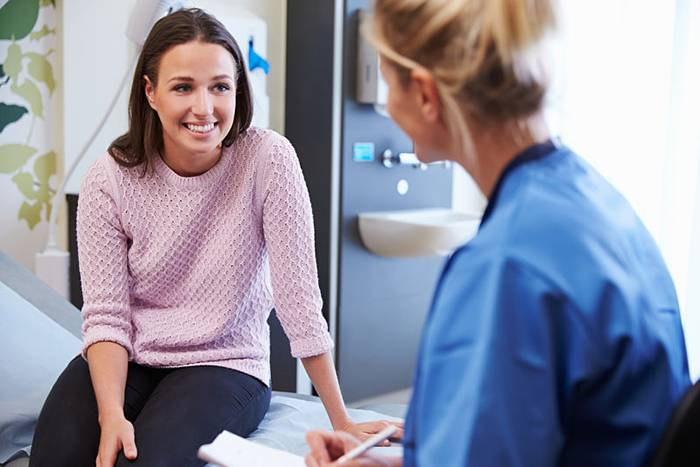 Female Patient And Nurse Have Consultation In Hospital Room